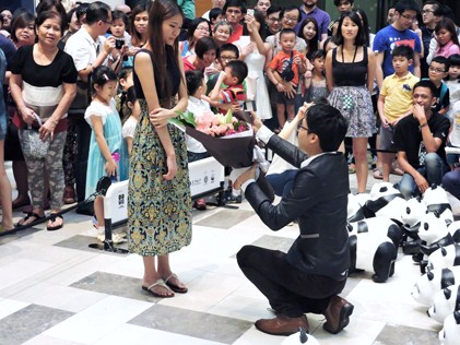 A gentleman goes down on one knee to make a marriage proposal
