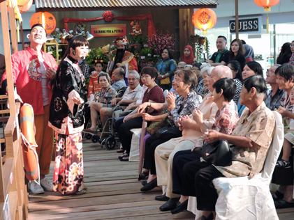 Performers cheer the senior citizens singing Chinese New Year songs