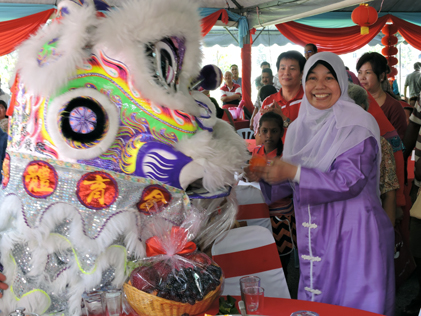Ampang MP Zuraida Kamaruddin receiving a mandarin orange from the lion at the PJS CNY 2015 open house