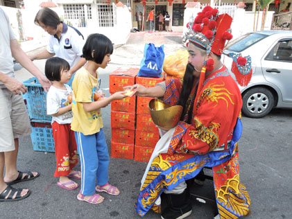 Feeling tired, the God of Prosperity sits on a stool giving out ang pow to children