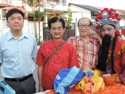 Gan Keng (second from left) with Tan Gim Tuan and Dato' Dr Wong Sai Hou posing with the God of Prosperity.