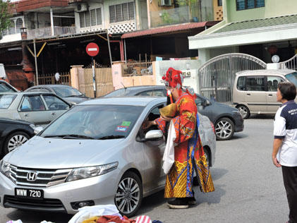 God of Prosperity handing out mandarin oranges to passing motorists in Sea Park
