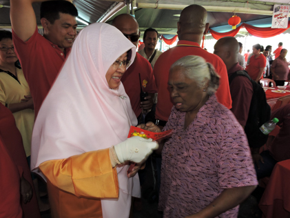 Haniza Mohd Talha handing out ang pow to visitors at PJS CNY 2015 open house