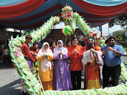 (L-R) Haniza, Zuraida, Hee and Rajiv and the God of Prosperity strike a pose with the dragon wrapped around them