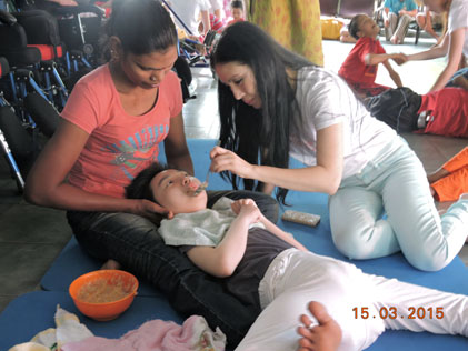 Miss Malaysia Tourism 1996 Zoee Tan feeding a 12-year old child born with cerebral palsy