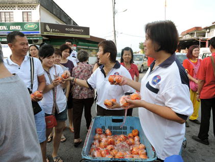 Rukun Tetangga Seksyen 21 Sea Park committee members distributing mandarin oranges to residents and passers-by.