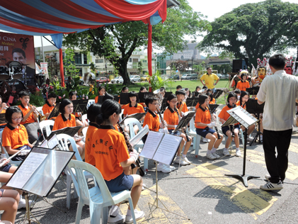 School children  performing orchestral music concert to the delight of the crowd