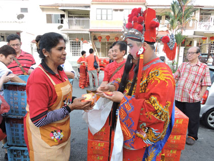 The God of Prosperity giving ang pow to every one in the community.