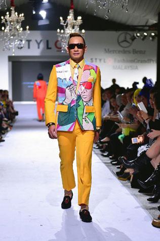 model walks the runway wearing a design by Fairuz Ramdan