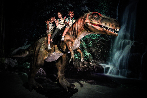 Children experiencing riding the T-rex