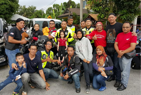 The group of bikers pose with 7-year-old Nur Firuza Amira (centre, in red shirt) during their visit to the family home.