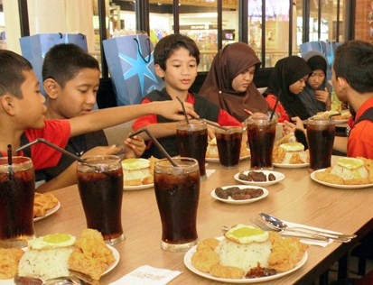 Children from Rumah Titian Kasih, Kuala Lumpur helping themselves to the buka puasa dinner at Pelicana Chicken restaurant