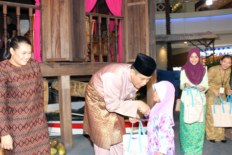 The Curve general manager Jazmi Kamarudin greeting and handing duit Raya and goodie bags to children from Rumah Perlindungan Al Nasuha.