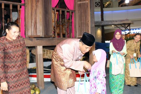 The Curve general manager Jazmi Kamarudin greeting and handing duit Raya and goodie bags to children from Rumah Perlindungan Al Nasuha.