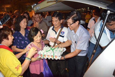 Ch'ng Soo Chau distributing eggs to senior citizens