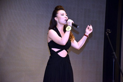"Contestant Eve Yap sings ""A Moment Like This"" during the talent show."