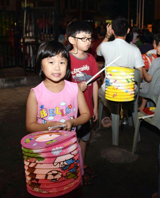 Excited children carrying lanterns during Mid Autumn Festival