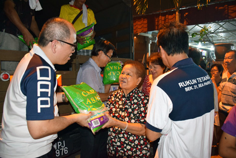 Kampung Tunku state assemblyman Lau Weng San distributing packets of rice to senior citizens.