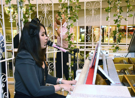 a vocal performer singing and playing the piano serenading the guests with her soft tunes