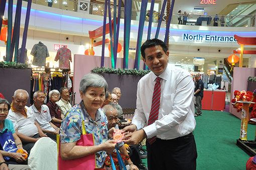 Jazmi Kamaruddin, General Manager of the Curve, giving out ang pows and goodie bags to the senior citizens.