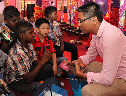 Encik Azizul Hisham Ahmad, Centre Manager of eCurve having a chat and giving out Ang Pows to the children.