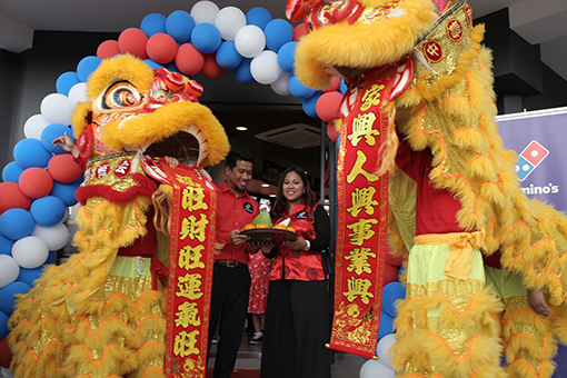 Lion dancers offering oranges and pamelo to Shamsul Amree, General Manager, Operations, Domino's Pizza Malaysia and Singapore (left) together with Linda Hassan, Deputy General Manager, Marketing, Domino's Pizza Malaysia and Singapore (right) as a symbol of prospertiy and good luck to usher in the upcoming Lunar New Year.