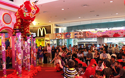 The lion dance troupe showing off their acrobatic skills to the excited children.