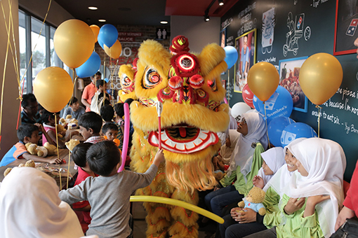 The lion dancers showing off their acrobatic skills to the excited children.