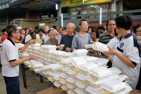 RT Sea Park committee members handing out satays packed in foam boxes to guests