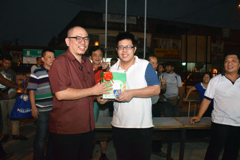 A resident receives his prize in a lucky draw from Lau Weng San