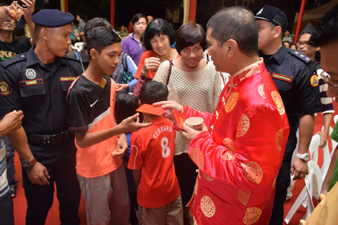 Azmin Ali distributing ang pow to young guests