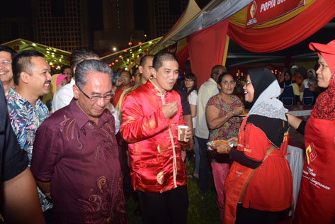 Azmin Ali trying out delicacies at the food stalls.