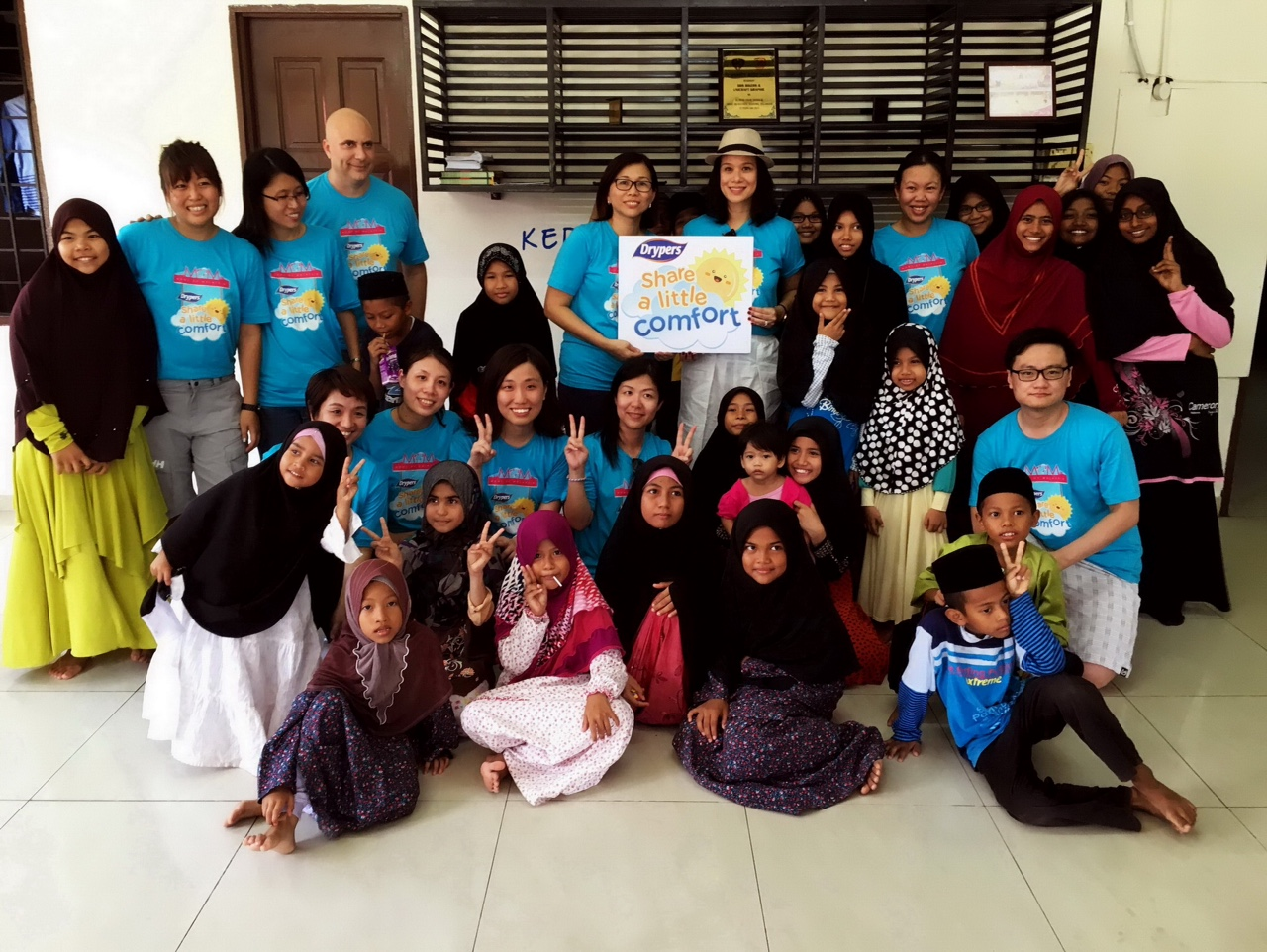 Evelyn Chan, Marketing Director of SCA Hygiene Marketing Malaysia Sdn Bhd (center left), Elaine Daly, Drypers' Moms of Malaysia (MOM) advocate (center right), volunteers with children at the orphanage