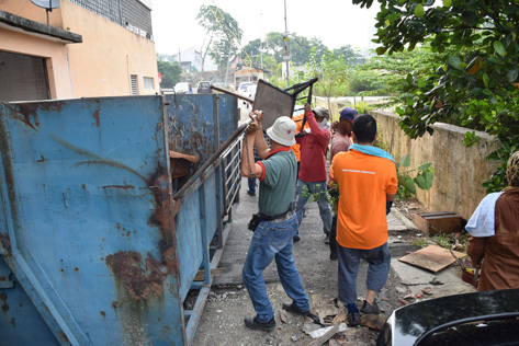 Residents and workers picking up discarded furniture during the gotong-royong.