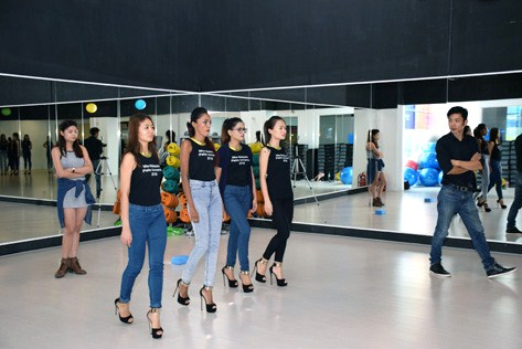 Contestants in 6-inch stilettos strut down a catwalk under the watchful eyes of their coaches