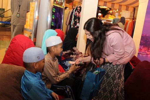 Gina Long Ahmad, Assistant General Manager, Leasing and Advertising and Promotions of eCurve handing out Duit Raya and Raya goodies to kids from Badan Kebajikan Siti Khadijah.