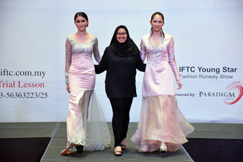 Siti Aminah Binti Sharuddin walks with models wearing her creations