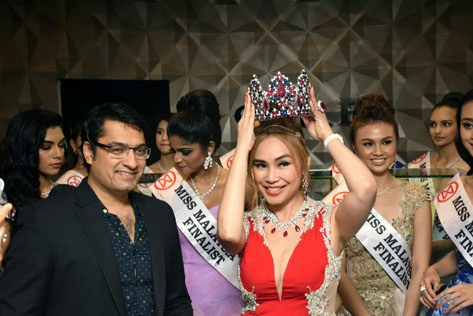 Dato Anna Lin holding the Miss Malaysia World 2016 crown on her head