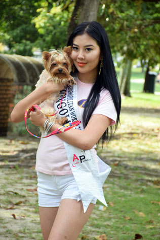 Miss Cosmopolitan World Mongolia 2016 - Anujin Sugirjav holding a crossed Silky Terrier with Yorkshire Terrier
