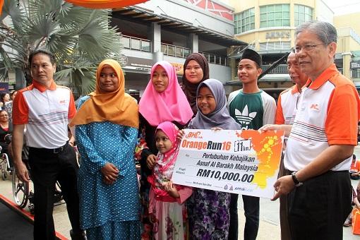 Tan Sri Dato' Seri Lodin bin Wok Kamaruddin presenting a mock cheque to Pertubuhan Kebajikan Asnaf Al Barakh Malaysia