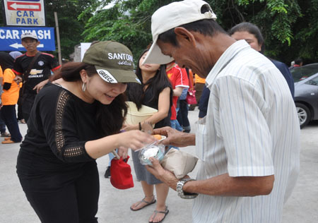Gina Long Ahmad, Assistant General Manager, Leasing and Advertising and Promotions of the Curve handing out food to the homeless at Jalan Panggung