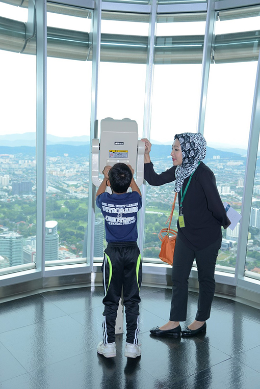 Siti Shazlina Shamsiruddin, Manager, Corporate Social Responsibility (right) with a student checking out the KL skyline from the Petronas Twin Towers Skybridge.